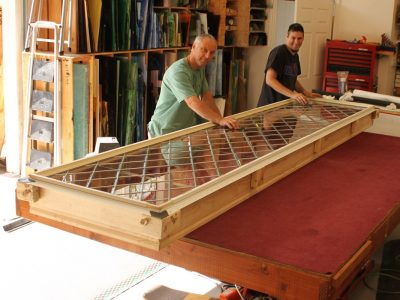 two workers moving glass